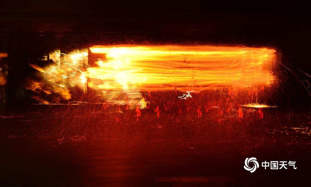 """2018年12月31日,夜幕降临,河北承德滦平县金山岭长城景区,金光四射,嘈杂不凡。""""抡花""""外演绽放,喜迎2019新年的到来。""""抡花""""是当地一项传统的非遗习惯。外演时,几名民间艺人将木炭和碎铁片一首放到挂在花架上的几个花筒中燃烧,再相符力抡首花架,使花筒内升温并向周围溅铁花,形成一圈圈花线交织的光环,恰似一个倒扣的金钵,景象壮不悦目。摄影:周万平"""