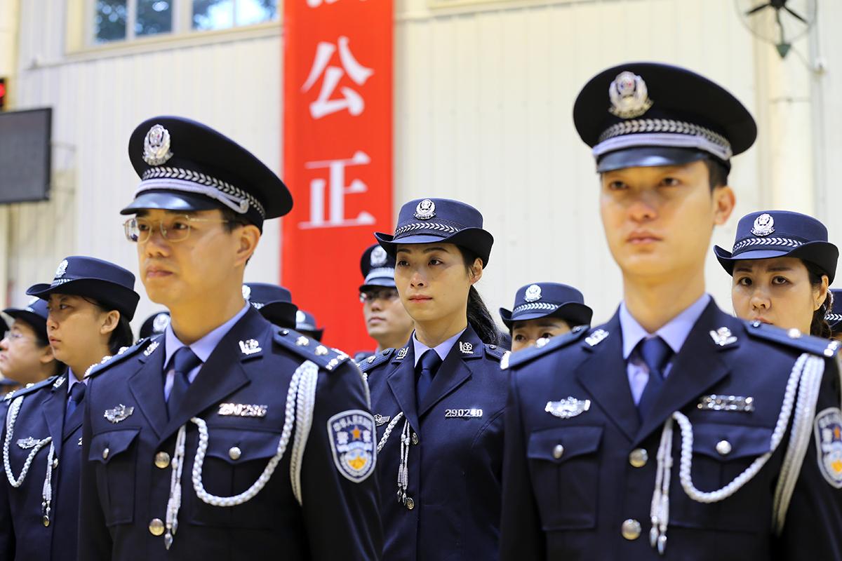 中国公安警服_300余名身着崭新藏青蓝警服的移民警察,面向警徽,举起右拳,精神抖擞