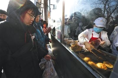 1月4日,京天红酒家,顾客排了三个多幼时的队后,买到了炸糕。 新京报记者 王飞 摄