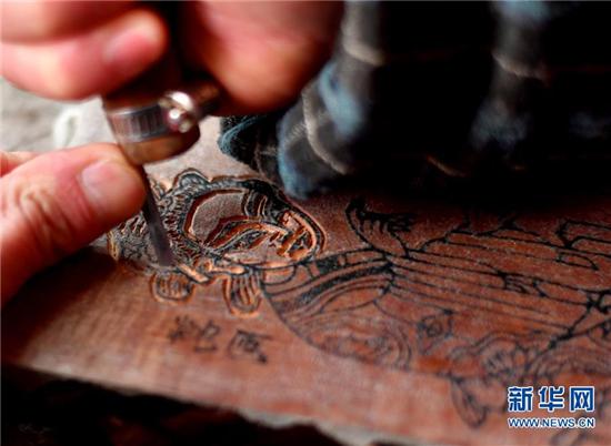 1月8日,开封市朱仙镇的年画艺人在雕刻印刷年画的木板。