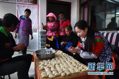 2月4日,松德村五社村民李玉花(右一)和家人一同包饺子。 新华社记者 张宏祥 摄