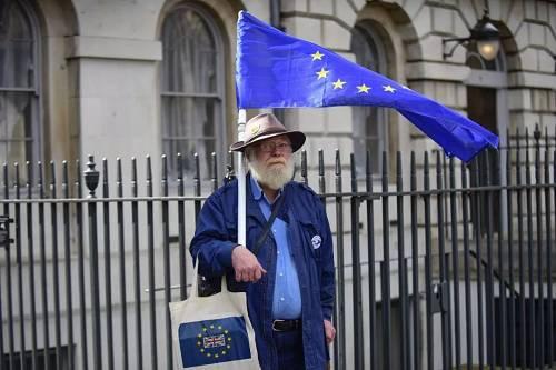 3月19日,在英国伦敦,示威者手持欧盟旗帜站在议会大厦外。(新华社)