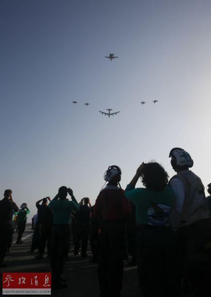 """""""林肯""""号航母地勤人员在甲板上观看B-52编队飞越。"""