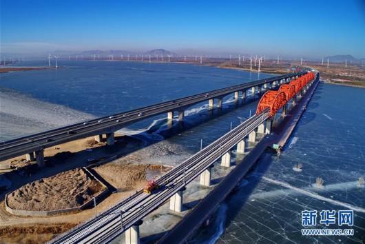 中铁三局工人在河北张家口京张高铁官厅水库特大桥进行铺轨作业(1月13日无人机拍摄)。新华社记者 杨世尧 摄