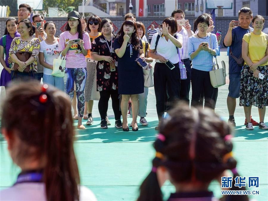 9月1日,在北京市东城区灯市口小学灯市口校区的开学典礼结束后,一年级新生在拍摄合影,家长也在一旁给孩子拍照留念,有的家长还在指导孩子如何摆姿势。