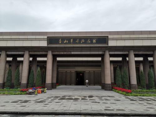"""香山脚下,新落成的香山革命纪念馆庄重大气,""""四梁八柱""""的雨棚造型寓意党中央在此为新中国搭建四梁八柱。"""