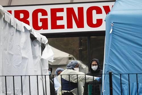 3月25日,纽约埃尔姆赫斯特医疗中心,一名医务人员引导一名患者进入新冠病毒检测站。图源:美联社