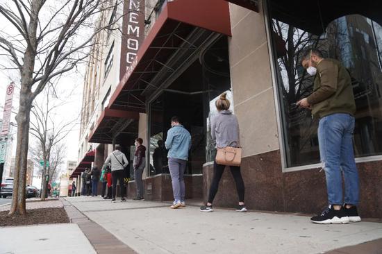 """4月4日,在美国首都华盛顿附近的弗吉尼亚州阿灵顿县,人们在一家超市外保持""""社交距离""""排队。(图片:新华社记者 刘杰 摄)"""